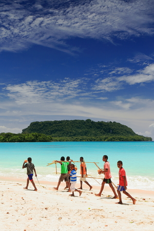 Port Olry, Vanuatu-October 19, 2014: Bunch of Ni-Vanuatu boys walk up the beach to reach the sand bar at its North end and cross to Malet island by foot at low tide. Espiritu Santo island-Sanma prov.