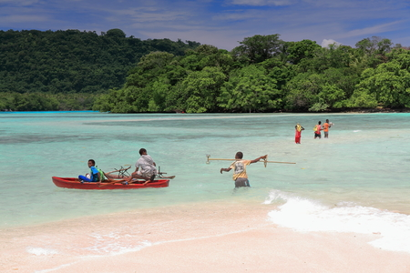 Port Olry, Vanuatu-October 19, 2014: Ni-Vanuatu boys cross by foot and boat at low tide the channel over the sand bar at the N.end of the beach to get to Malet island-Espiritu Santo island-Sanma prov.