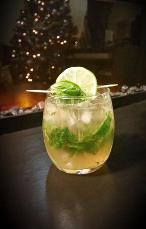 Winter Island Vacation- 1 12 oz. 45 mL whiskey  12 oz. 15 mL lemon juice  12 oz. 15 mL simple syrup  5 basil leafs  Ginger ale  Lime slice and basil lead garnish