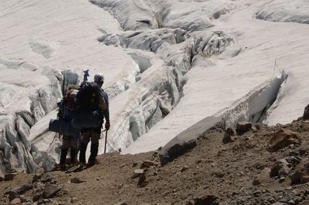 crevasse: Two mountain climbers looking at a crevasse Stock Photo