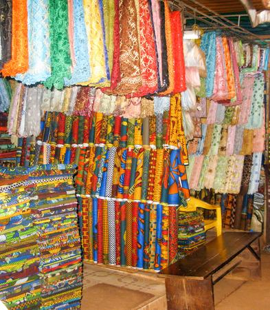 market stall: Nigerian fabrics line a market stall in Enugu Nigeria Stock Photo