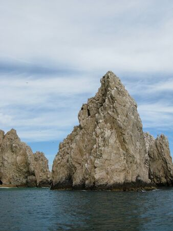lucas: Rocks at Lands End in Cabo San Lucas Mexico with a partly cloudy sky Stock Photo