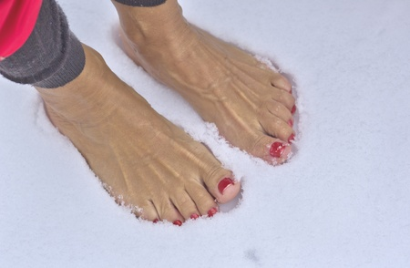 Woman standing barefoot in fresh snow
