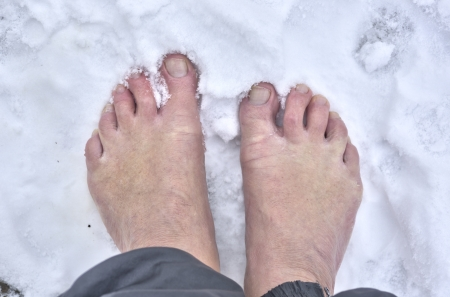 Man standing barefoot in fresh snow