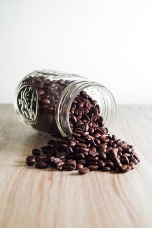 Spilled coffee beans from mason jar on wood grain texture Zdjęcie Seryjne
