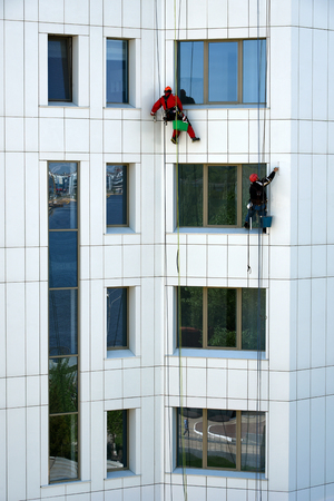 workers wash the facade of a high-rise building