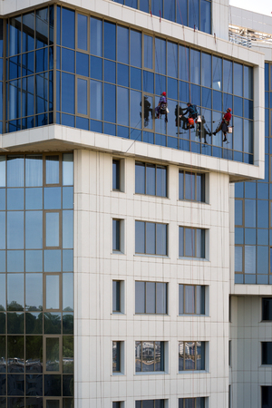 high-altitude work workers wash the facade of a building Zdjęcie Seryjne