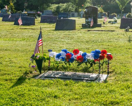 A single grave with an American Flag and red, white and blue carnations