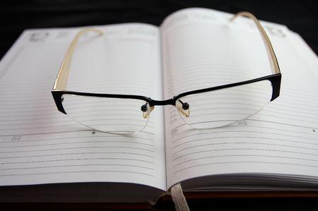 eyeglasses on notebook on black