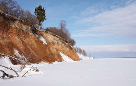 Winter landscape. Lone fir on a steep bank of a frozen river. Stock Photo