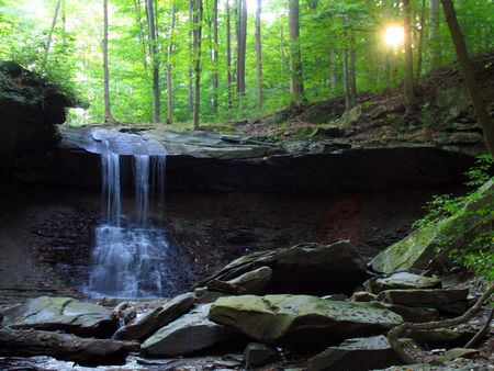 Waterfall and setting sun deep in the forest photo