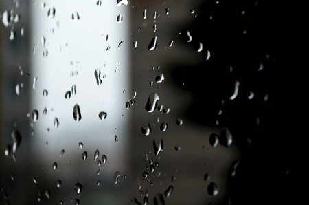 rains: Water drops running down the window while it rains outside