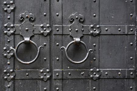 Metal rusty round handle on black wooden door. Top view. Stock Photo