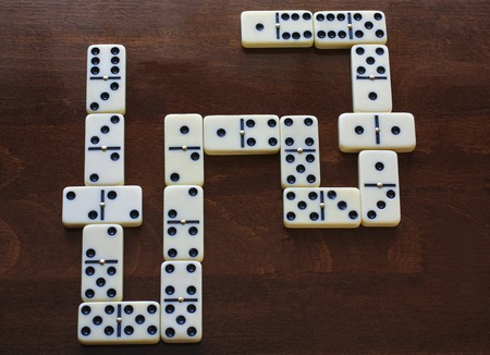 domino pieces on the brown wooden table background.