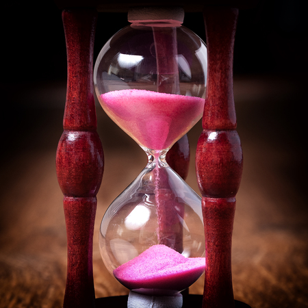 ancient pass: Close-up Hourglass on wood background, antique tone. Stock Photo