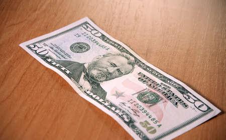 ben franklin money: Closeup of fifty dollar bills on wooden table. Fifty dollar