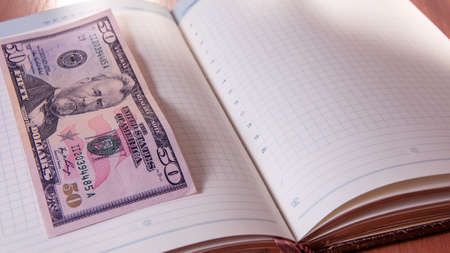 Fifty American dollars and Notepad on wooden table. Fifty American dollars and Notepad Stock Photo