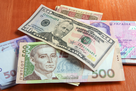 economic rent: Ukrainian and maryanska currency on the table. Dollars and hryvnia