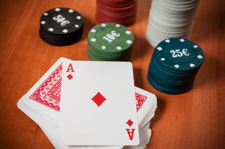 lear: Poker chips and generic playing cards. Courts for poker chips and dice on wooden table