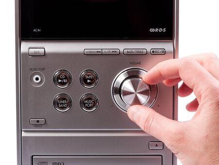 controlling: Hand controlling volume of a stereo recorder. Hand controlling volume Stock Photo