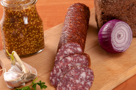 salame: Sausage sliced with a knife on a wooden table. Sausage on wooden table Stock Photo