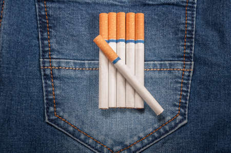 boodle: Pack of cigarettes and lighter in pocket of jeans. Closeup