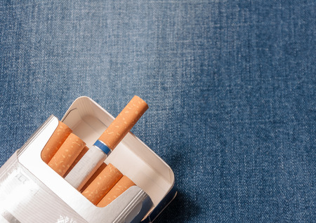 boodle: Closeup to jeans pocket with cigarettes. Cigarettes in blue denim