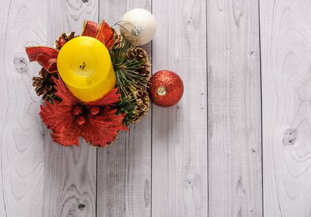 A yellow candle and a New Year pine wreath on an old wooden background. Standard-Bild