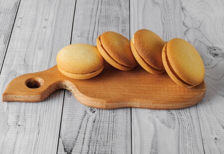 Delicious biscuits with banana filling on an old wooden table. Sweet dessert.