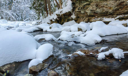 Waterfall in winter. Mountain river and snow on the mountain slopes