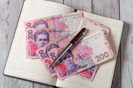 Notepad, pen and money on a light wooden background 版權商用圖片