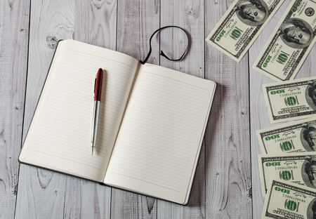 Notepad, pen and money on a light wooden background Foto de archivo