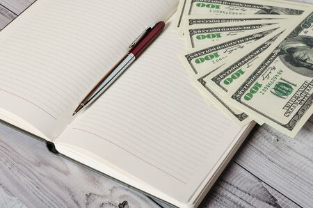 Notepad, pen and money on a light wooden background.