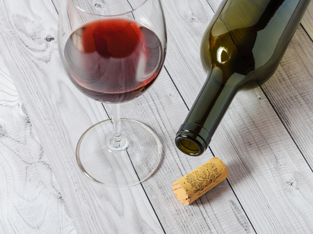 Red wine in a glass and a bottle on a light wooden table. 版權商用圖片