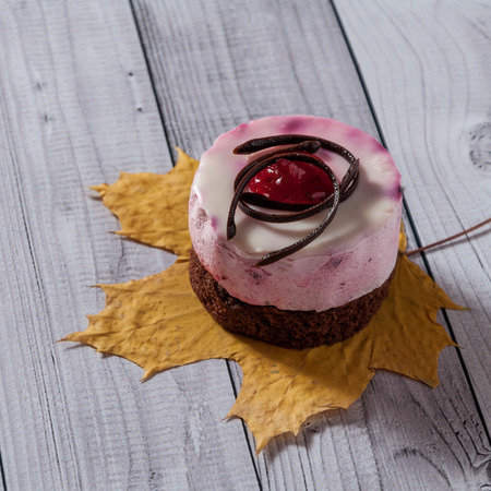 Fresh cherry cake round shape on a light wooden background. Biscuit cake on a wooden table