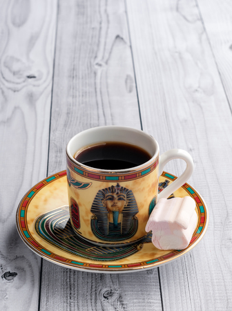 A Cup of coffee with Egyptian patterns and sweet marshmallows on a light wooden background 版權商用圖片 - 119134783