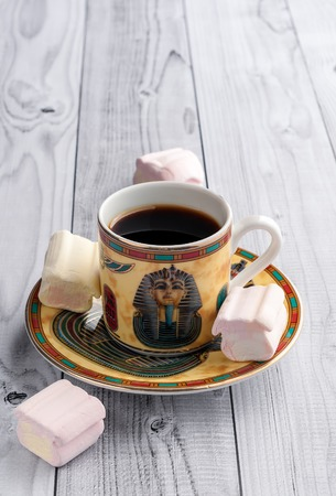 A Cup of coffee with Egyptian patterns and sweet marshmallows on a light wooden background 版權商用圖片 - 119134787