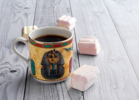 A Cup of coffee with Egyptian patterns and sweet marshmallows on a light wooden background