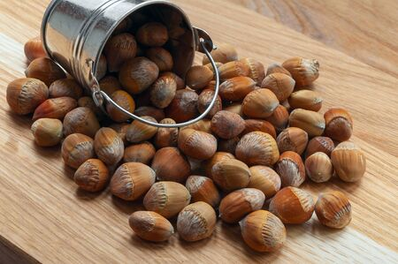Hazelnuts in a small bucket on a wooden table.