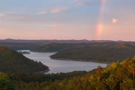 A rainbow in the sky during a beautiful sunset at Broken Bow Lake, Oklahoma. Stock Photo