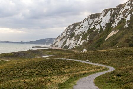 A footpath meanders through a grassy field next to the White Cliffs of Dover. Stok Fotoğraf