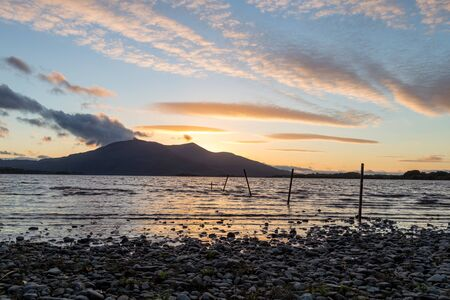 The sun sets over Cow Island in Lough Leane next to Killarney, Ireland.