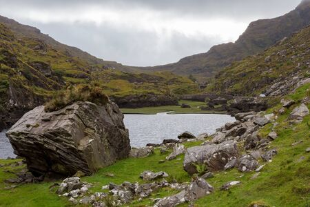 A Lake with a large rock in Dunloe Pass