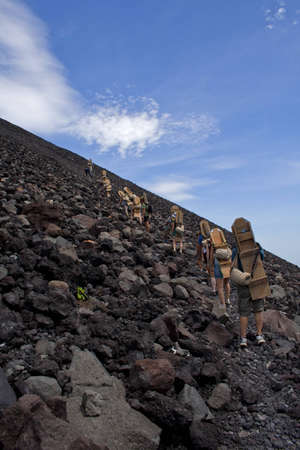 A group of volcano boarders climbing up the volcano Cerro Negro, near Leon Nicaragua, on their way to sliding down it