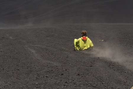 A girl volcano boarding down a black rock volcano
