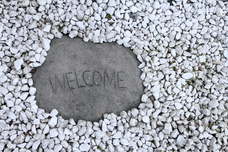 A large stone welcome sign surrounded by little white rocks Stock Photo - 16651404