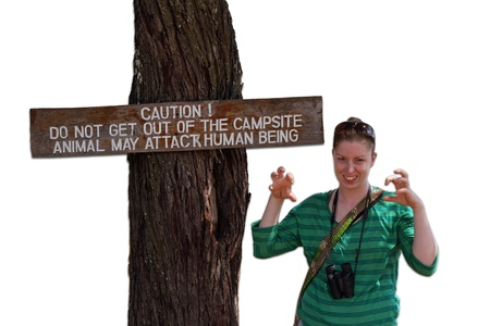 cautions: A woman pretends to be a scary animal next to a sign that cautions humans that animals may attack if you leave the campsite.