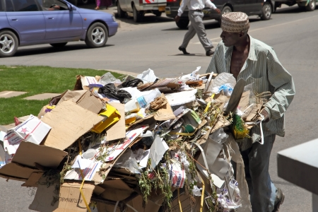 mwanza: A African man in Mwanza, Tanzania pushing a cart full of cardboard boxes and trash