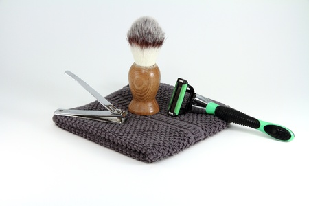 Items for a simple or rugged mens grooming and shaving.  Items include razor, nail clippers, towel, and shaving cream Stock Photo