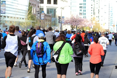 kilometer: VANCOUVER, CANADA - April 21, 2013 -Participants of the 2013 Vancouver Sun Run head away from the start line into the 10 kilometer course in Vancouver, Canada